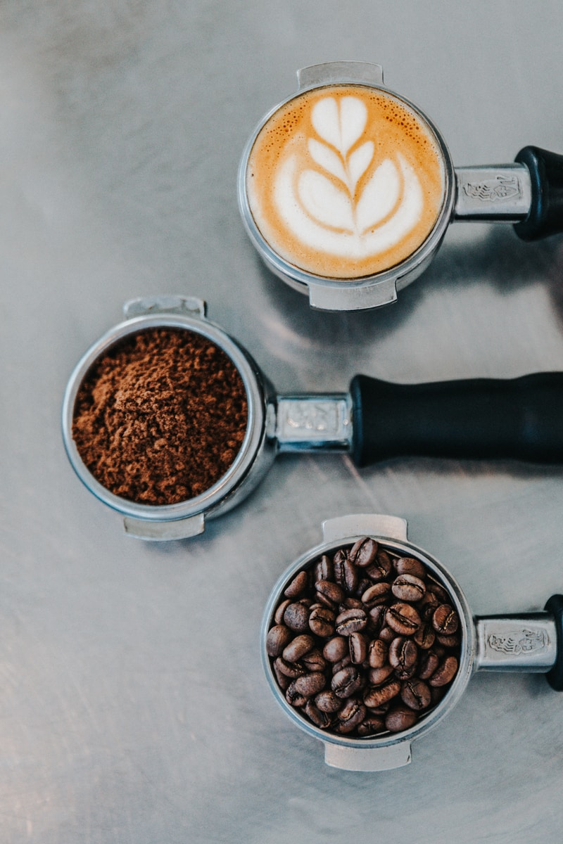 flat lay photography of coffee latte, ground coffee, and coffee beans